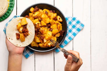 Traditional mexican potatoes with chorizo on white background
