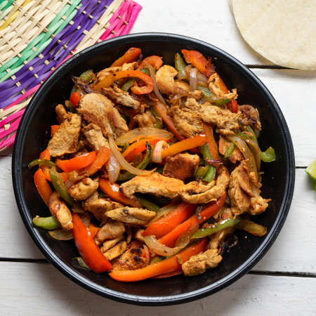 Traditional mexican chicken fajitas on white background