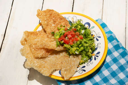 Traditional mexican guacamole with pork chicharron on white background