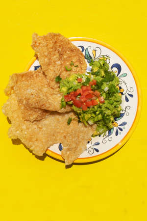 Traditional mexican guacamole with pork chicharron on yellow background