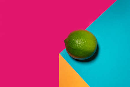 Green lime fruit on modern colorful background