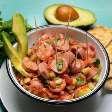 Wieners cocktail with avocado and ketchup on turquoise background. Traditional mexican food Stock Photo
