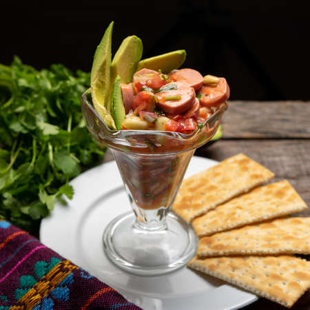 Wieners cocktail with avocado and ketchup on wooden background. Traditional mexican food Stock Photo