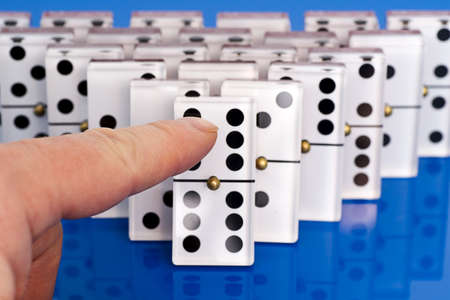 Dominoes on Blue with a Finger Pushing Them