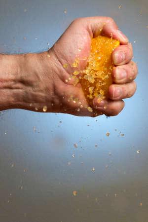 Male Hand Squeezing an Orange Stockfoto