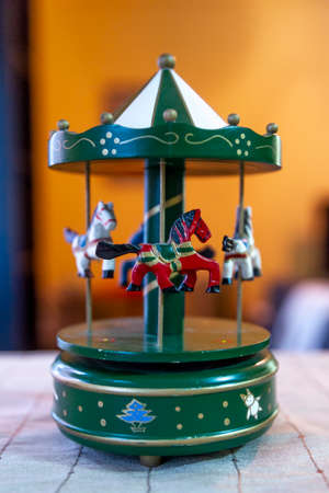 Old metal merry-go-round toy whith green little horses.