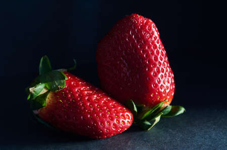 two strawberries with natural light and black background
