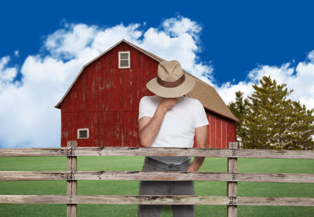 sad farmer with a red barn in the back Banco de Imagens