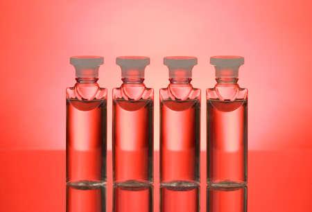 lit: Four bottles back lit on red background