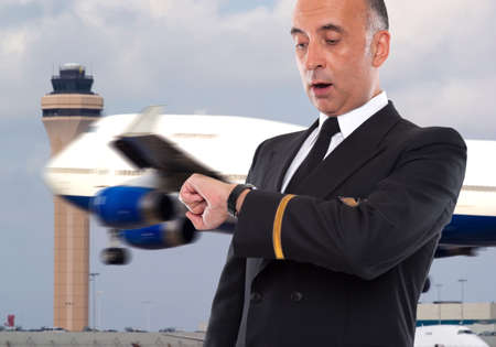 pilot wings: Handsome airline worker looking at his watch Stock Photo