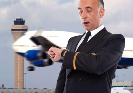 piloto de avion: Trabajador hermoso línea aérea que mira su reloj