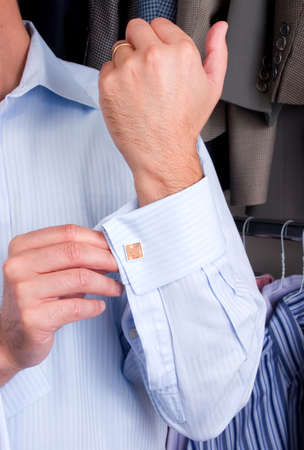 businesswear: A man putting on his cuff links Stock Photo