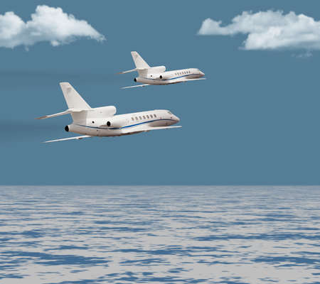 Two private jets flying over the ocean