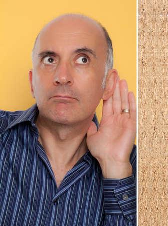 nosey: Man listening through the wall