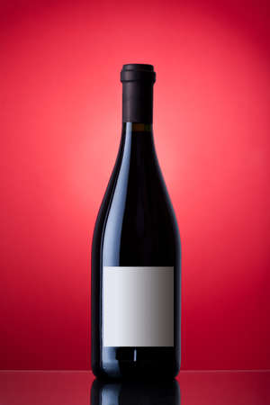 Unopened wine bottle on a red background