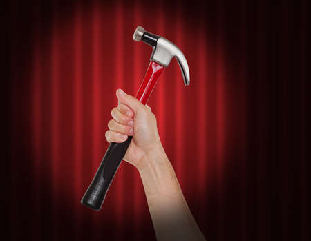 housebuilding: Hand holding a hammer in the spot light