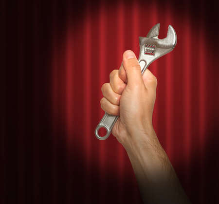 iron curtain: Hand holding a wrench under a spot light