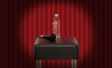 Bottle of water next to a microphone on a stool in the stage