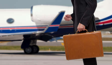 corporate jet: Businessman standing in front of corporate jet