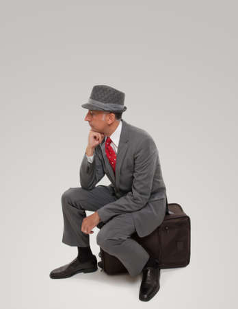 business traveler: A business traveler waiting seating on a suitcase