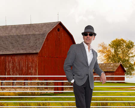sunglassess: Fashionable man standing in from of a red barn
