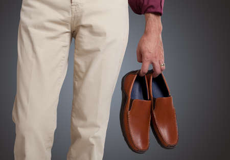 mens shoes: Man holding the shoes in hand close up