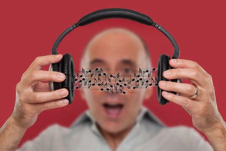 visualizing: Man listening and visualizing music from headphones.
