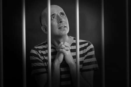 clemency: Man asking for mercy in prison Stock Photo