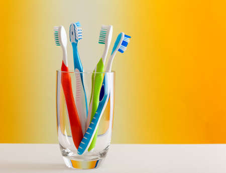 Glass holding colorful toothbrushes
