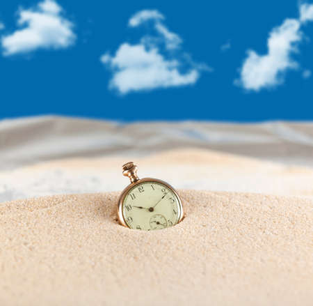 ancient pass: Vintage pocket watch semi buried in the sand Stock Photo