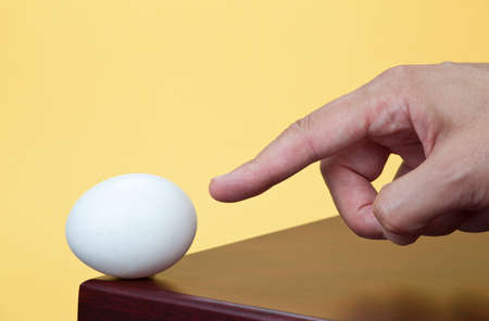 Finger pointing to an egg