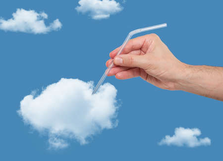 scarce resources: Hand putting a straw in a puffy cloud
