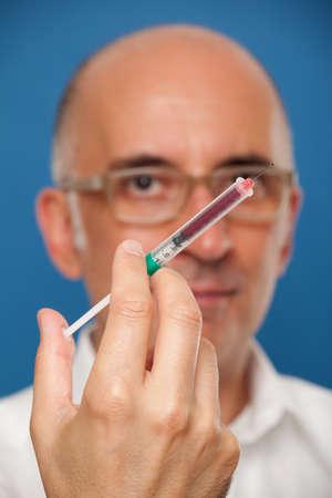 Man holding a syringe up close Archivio Fotografico