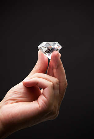 Close up of a hand holding a diamond