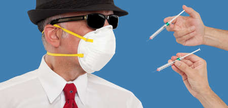 needle syringe infection: Man wearing a mask being vaccinated Stock Photo