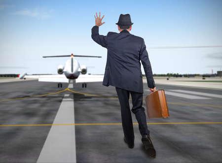 飛行機の背後に実行しているビジネスの男性