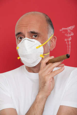 smoking a cigar: Man smoking a cigar wearing a mask Stock Photo