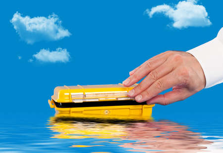 watertight: Opening a water resistant case floating in the water Stock Photo