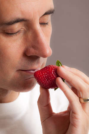 Face of attractive man smelling strawberry with closed eyes