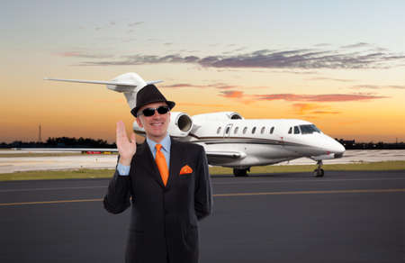 Business man waving near a private jet
