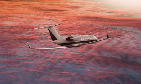 Private jet flying over a sunset sky Stock Photo
