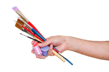 Hand holding several brushes and paint