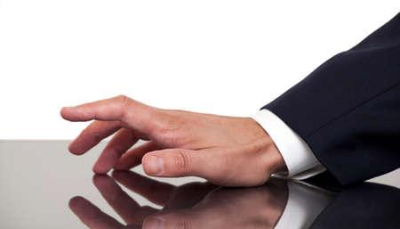 ビジネス人間の手の指を机の上でコツコツと
