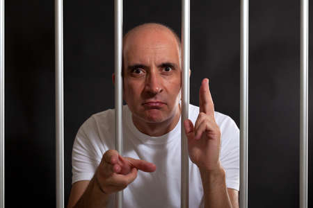 incarcerated: Man in jail gesturing guns with his hands