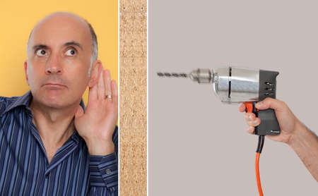 nosey: Man leaning against a wall listening to a drill Stock Photo