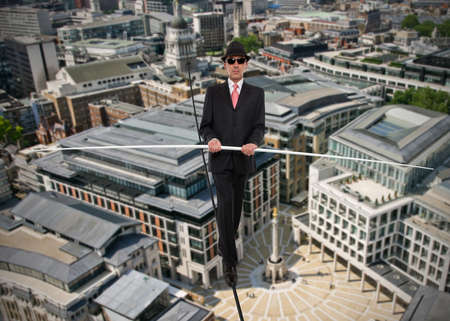 equilibrium: Business man in equilibrium on a rope over a city Stock Photo