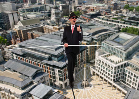 Business man in equilibrium on a rope over a city 免版税图像