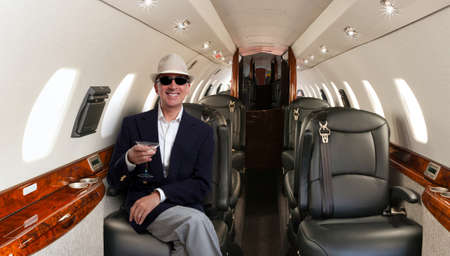 自信を持って成熟した男性民間の飛行機で彼の席に座っていると笑顔