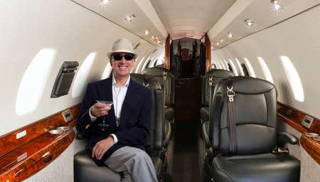 Zekere rijpe man zit aan zijn zetel in privé vliegtuig en lachend