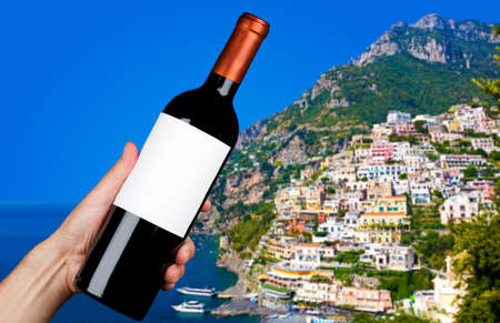positano: Hand holding a bottle of red wine in Positano